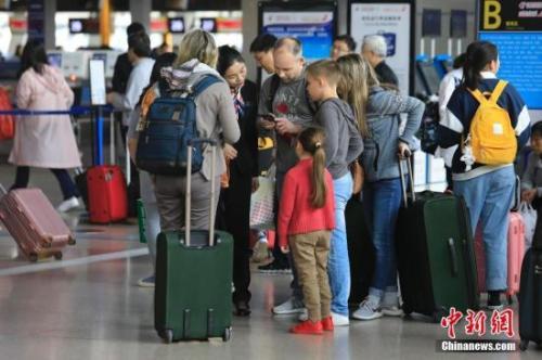 资料图为外籍游客在浦东国际机场T1航站楼向工作人员询问相关业务。 殷立勤 摄