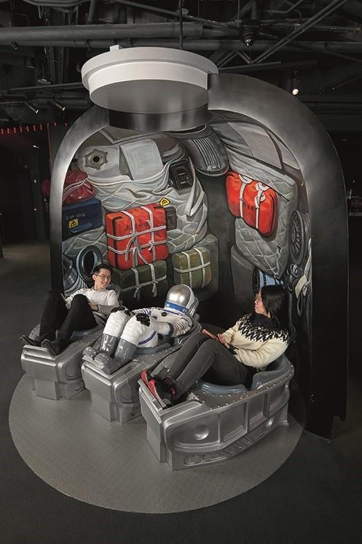 """躺卧在""""神州号太空船返回舱""""内,拍摄生动的照片 (图片来源:香港太空馆官网)"""