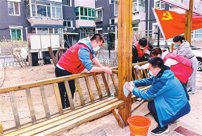 4月10日,在沈河区青年小区南苇巷30号院,在职党员和志愿者在擦拭长亭。 张文魁摄