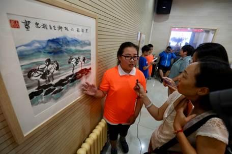 (来自<a href='http://travel.sina.com.cn/beijing-lvyou/?from=b-keyword' target='_blank'>北京</a>西什库小学的小策展人为观众们介绍玉树小朋友作品)