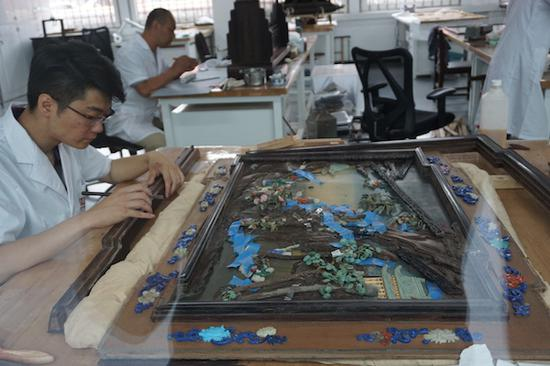 木器修复室的老师在修复一件插屏的边框