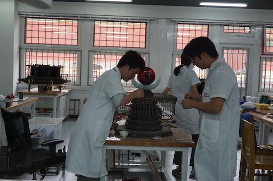 木器修复室的老师们在对一件紫檀塔的部件进行除尘和清洗