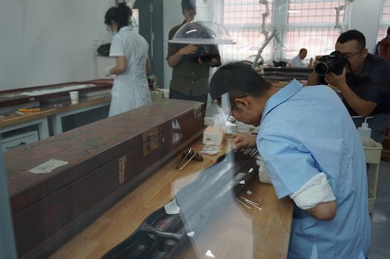 透过玻璃可以看到漆器组的老师在修复清洗一件漆器