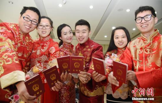 图为新人们一同展示结婚证。中新社记者 翟羽佳 摄