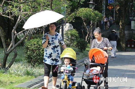 昨天,福州现今年来首轮高温,市民撑伞出行。郭超燕 摄