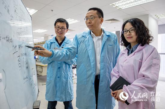 无锡物联网产业研究院院长刘海涛(中)与团队成员一起研讨