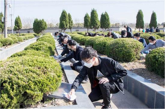 图为志愿者们在擦拭墓碑