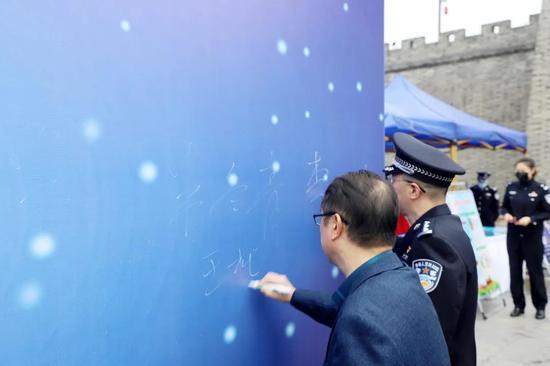 出席活动的领导在签名墙上签字