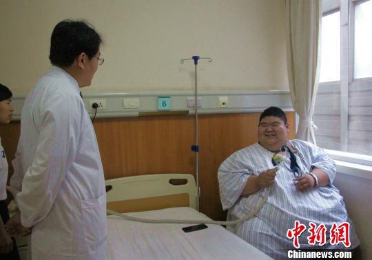 """19岁的山东莱芜小伙王浩楠凭借688斤的""""重量""""走红网络,目前已入院治疗,渴望减到200斤。图为王浩楠与他的主治医生正在交流治疗方法。 赵晓 摄"""