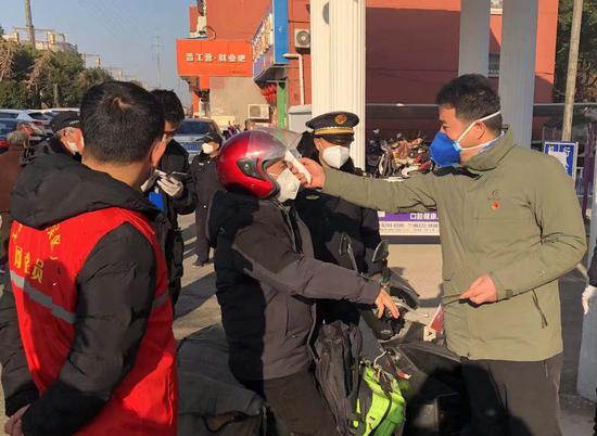 王友金在泰伯一社区大门口给外来人员检测体温