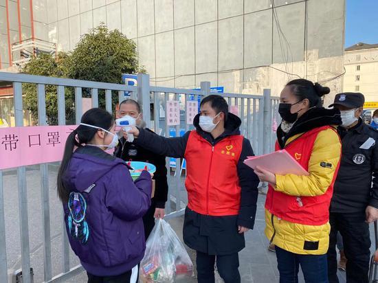 审计科青年党员须宇峰在门岗测量出入人员体温