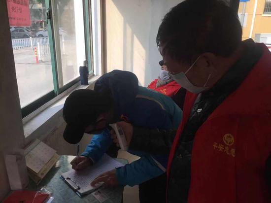 泰伯一社区志愿党员吕勤南为出入人员测量体温