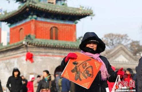 资料图:农历腊月廿三小年儿来临,北京东岳庙举办迎新春送春联活动,参与者甚众。中新社记者 富田 摄_副本