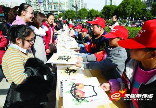 图为学生代表在慈善募捐活动上义卖书画作品献爱心。   商报记者宦玮/摄