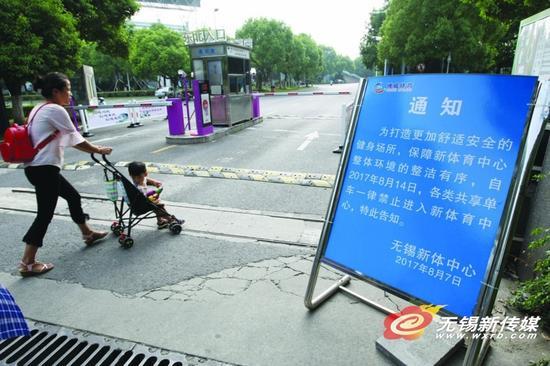 15日,市民推着童车进入新体育中心,入口旁摆放着禁止共享单车进入的通知牌。