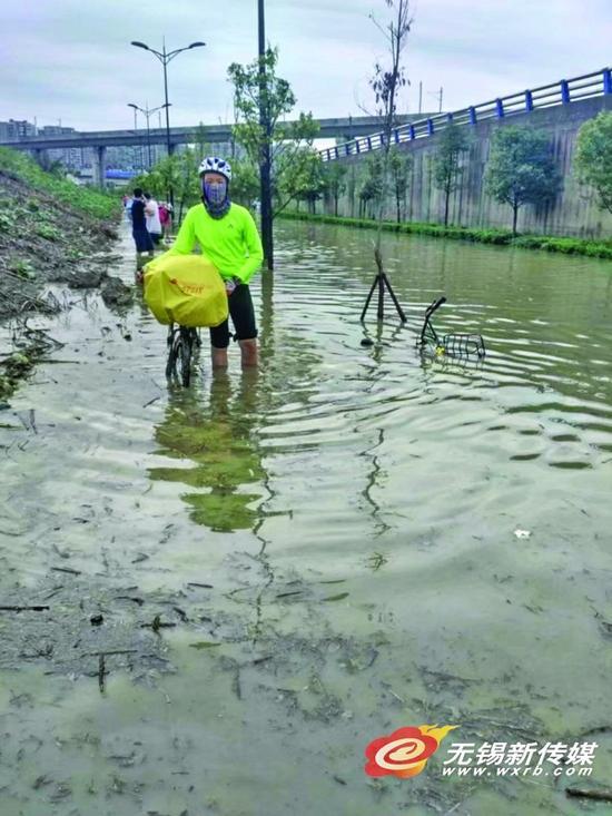 周瑀烨在成都积水的马路上推车。