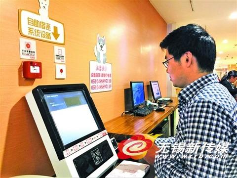 市民在自助设备前借书。