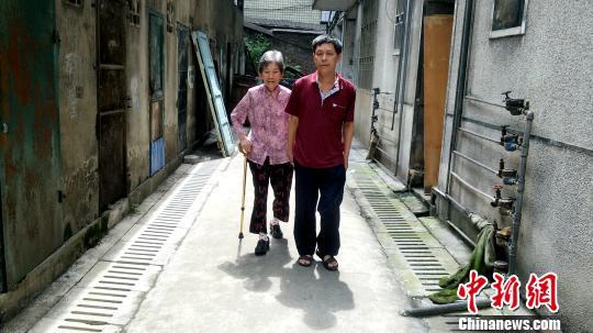 只要不下雨,每天早上8点,彭建国都会牵着母亲张喜秀出去散步。 徐志雄 摄