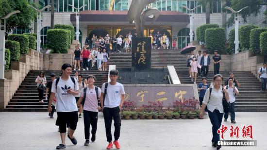 资料图:6月8日,广西南宁第二中学考点外,考生轻松走出考场。当日,全国部分地区2018年高考结束。 中新社记者 俞靖 摄