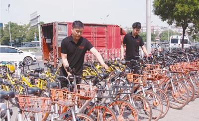 摩拜单车北京丰台区运维主管肖金睿(左)正在摆放单车。 邱超奕摄