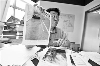 杨晓在展示自己收集的相关证据 摄影/本报记者 袁艺