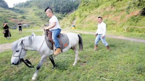 黄金星在牧场教儿子骑马。 本报记者 邹飞 摄