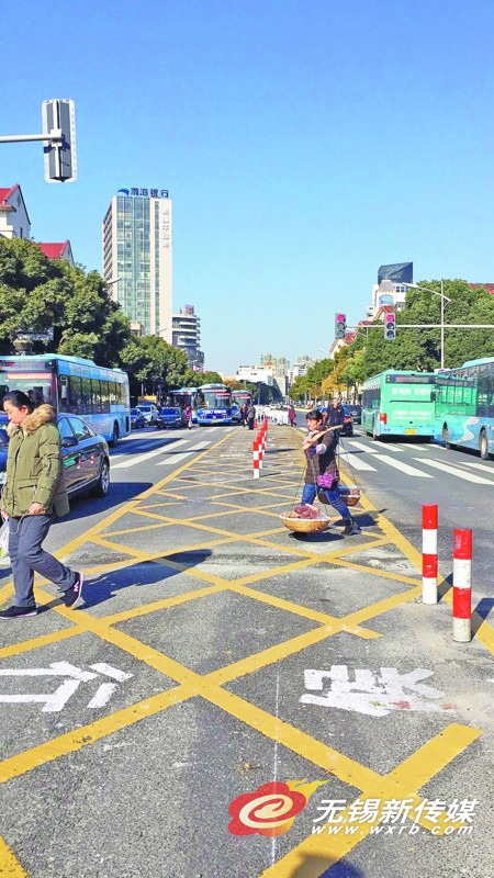 如果在过马路时行人横道信号灯由绿灯变为红灯,行人可在二次过街区域等候下一次绿灯通行,确保过街更加安全。 (杨柳 图文报道)