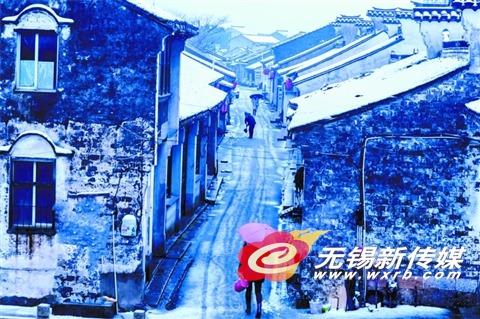 在惠山区玉祁街道,市民从覆盖着一层薄雪的礼社古街街头走过。