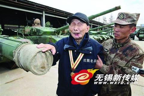 钱建民(左一)在部队官兵的搀扶下摸了坦克。