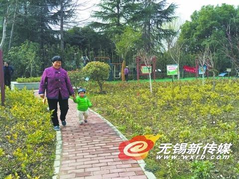 """新建的城市游园内有花草树木、石椅廊亭、健身器材等设施,附近居民一出家门就可见绿,享受""""绿色福利""""。   (宦瑾 摄)"""