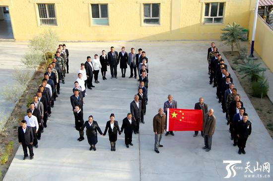"""民丰县安迪尔乡繁荣村,58名党员以""""10.1""""为型与国旗合影。"""