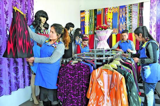 11月28日,在洛浦县恰尔巴格乡奥依拉村卫星工厂就业的村民,在产品展示厅整理服装。本报记者约提克尔·尼加提摄