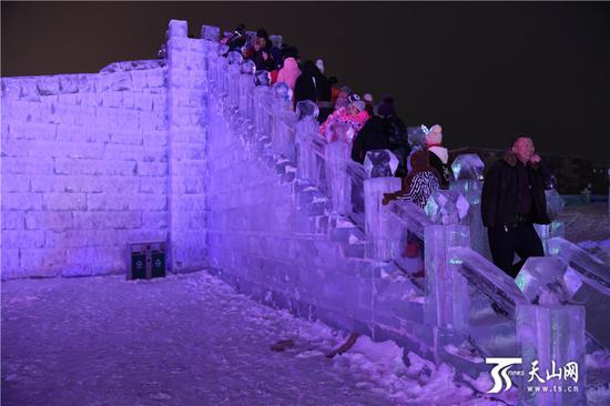 2019-11-20晚,众多游客在阿勒泰市冰雪大世界登上滑梯准备滑雪。