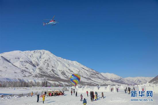 2月9日,游客在喀纳斯景区禾木雪乡乘直升机升空观光。新华社发(雷东翔 摄)