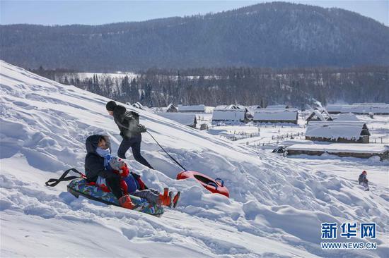 2月9日,游客在喀纳斯景区禾木雪乡体验雪圈滑雪。新华社发(雷东翔 摄)