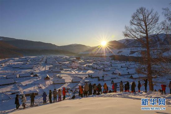 2月9日,游客在喀纳斯景区禾木雪乡拍摄落日。新华社发(雷东翔 摄)