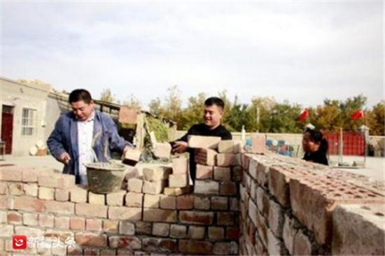 热比克·吾甫(中)帮助张铁欣(左)修房子