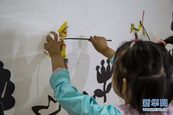 6月1日,孩子们在现场体验传统皮影戏。 新华网杲均丰 摄