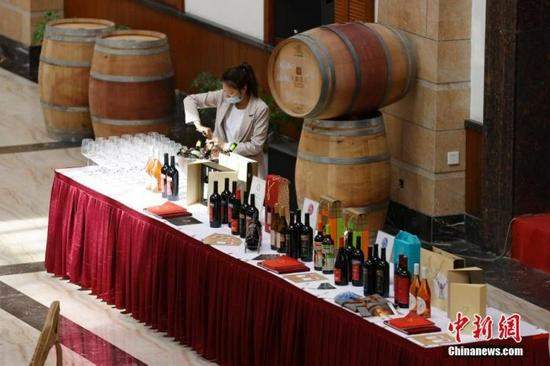 图为9月24日拍摄的新疆天塞酒庄工作人员开启红酒。中新社记者 富田 摄