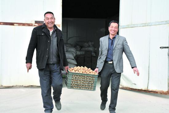 3月20日,莫合塔尔与赵武忠(右一)在搬运准备销售的核桃。
