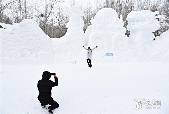 2019年1月12日,在桦林雪世界,游客与雪雕合影。