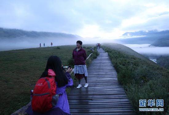 图为清晨来此赏日出的游客正在拍照留念。新华网 刘舒 摄