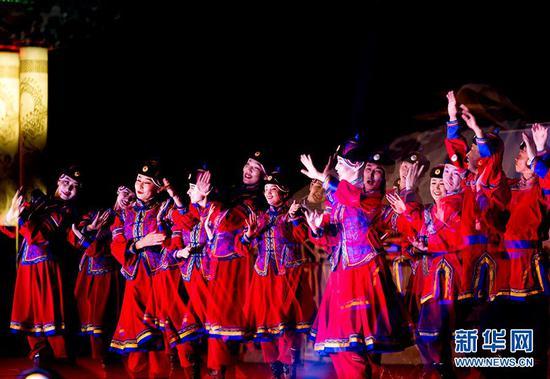 5月31日,在博湖县天湖湾广场的舞台上演员们随着音乐舞动着。