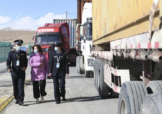 在新疆卡拉苏口岸,喀什地区外事办公室工作人员与卡拉苏出入境边防检查站执勤民警一起检查出境车辆(10月16日摄)。