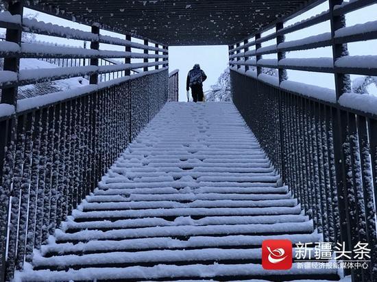 天桥阶梯被雪覆盖,一片洁白。