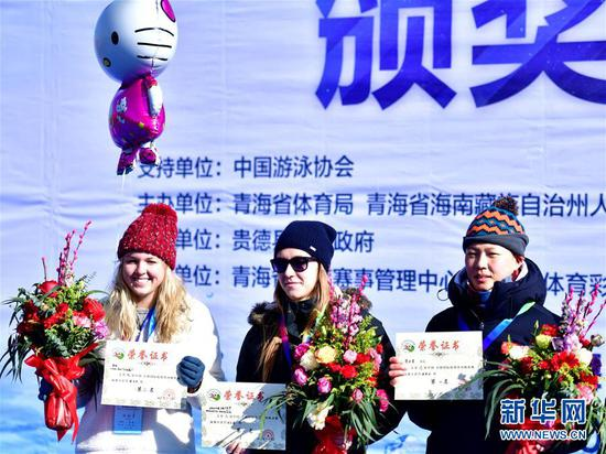 1月6日,获得女子A组三甲的俄罗斯队选手卡里帕切娃·马勒卡丽塔(中)、中国队选手苏天赏(右)、美国队选手劳伦在颁奖台上合影。 当日,第九届中国·青海国际(冬季)抢渡黄河极限挑战精英赛在青海省海南藏族自治州贵德县举行,赛事吸引了来自俄罗斯、法国、德国等17个国家和地区的122名冬泳爱好者参与。 新华社发(张龙摄)