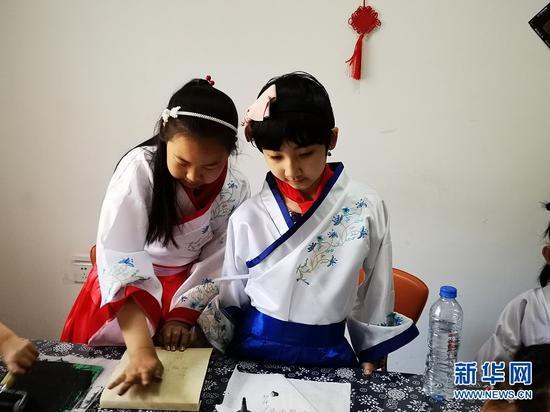 6月1日,孩子们在现场体验活字印刷术。 新华网周倩 摄