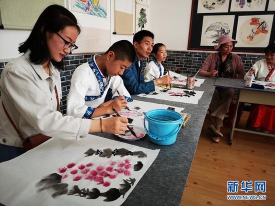 6月1日,孩子们在老师的带领下学习国画。 新华网周倩 摄