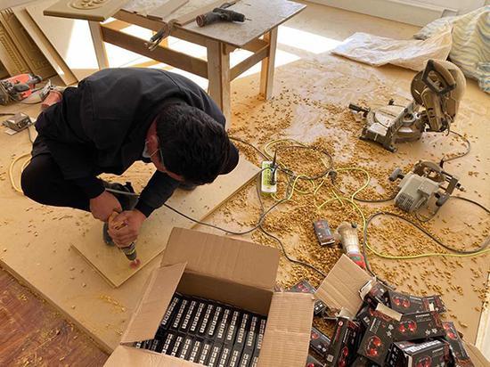 阿西尔·塔依尔正在为社区里居民的新房装修。新华网 梁甜甜摄