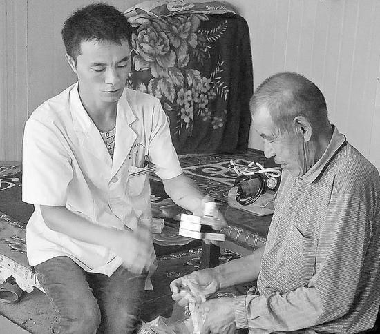 文中图:马生俊(左)为牧民阿尔恒送来药品、检查身体(资料图片)。